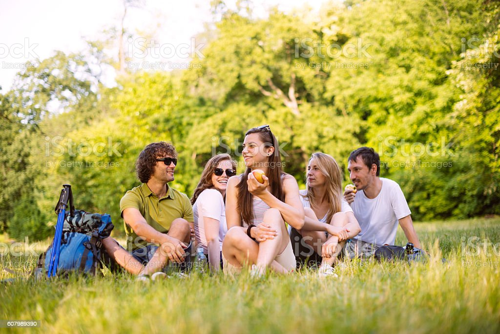 Five young people relaxing in park after hiking stock photo