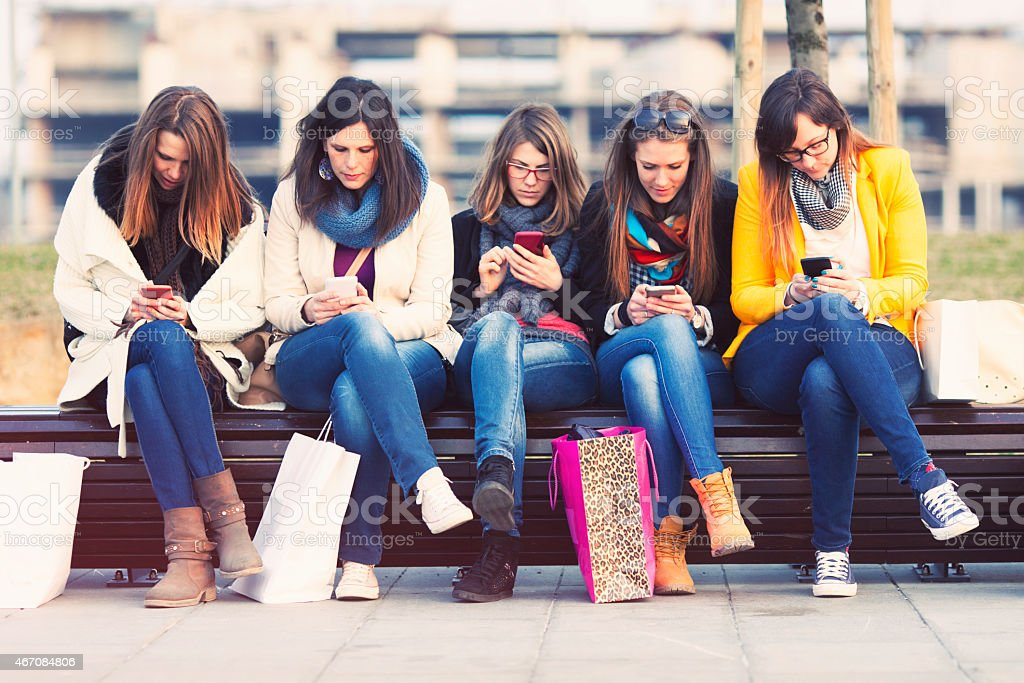 Five young women using smartphones at a mall stock photo