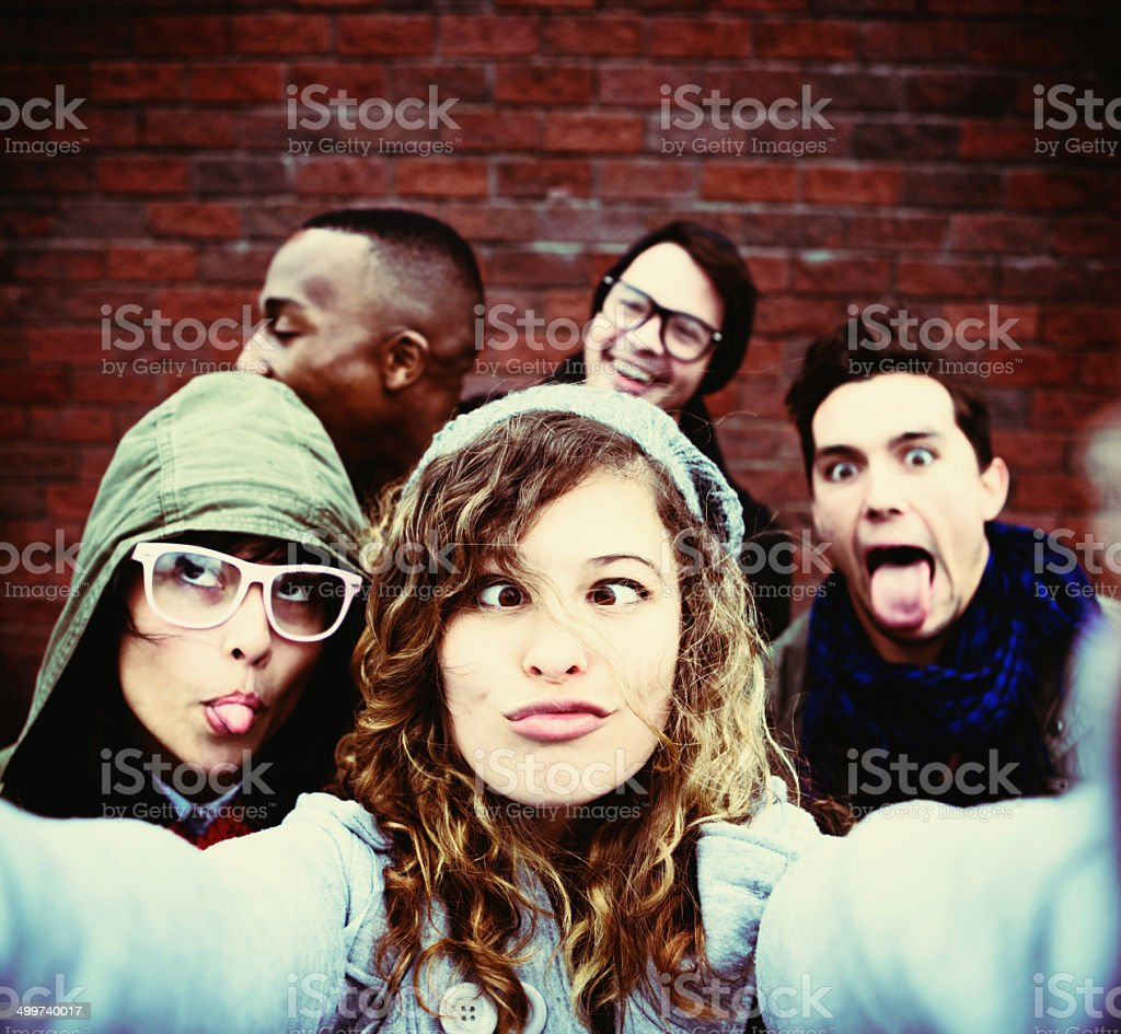 Five youngsters grimace,  taking very silly selfie stock photo
