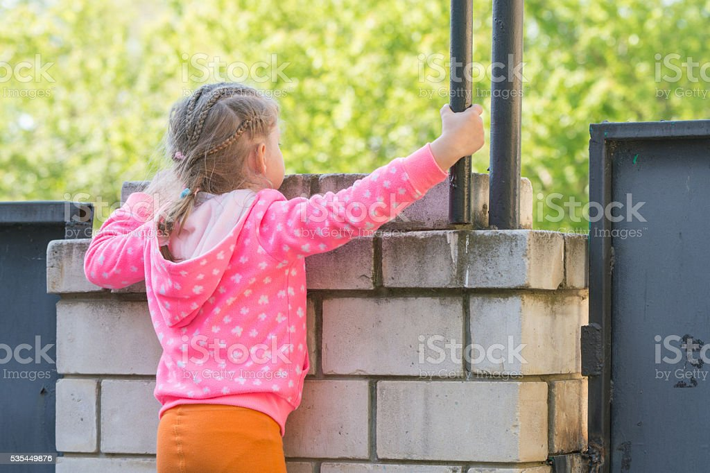 Five-year girl climbed on a brick fence and looks for stock photo