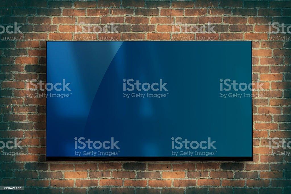 TV fixed on the brick wall stock photo