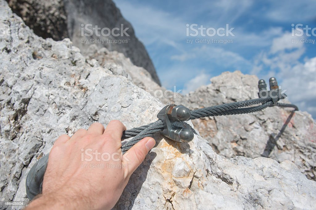 fixed rope route on mountain ridge with hand stock photo