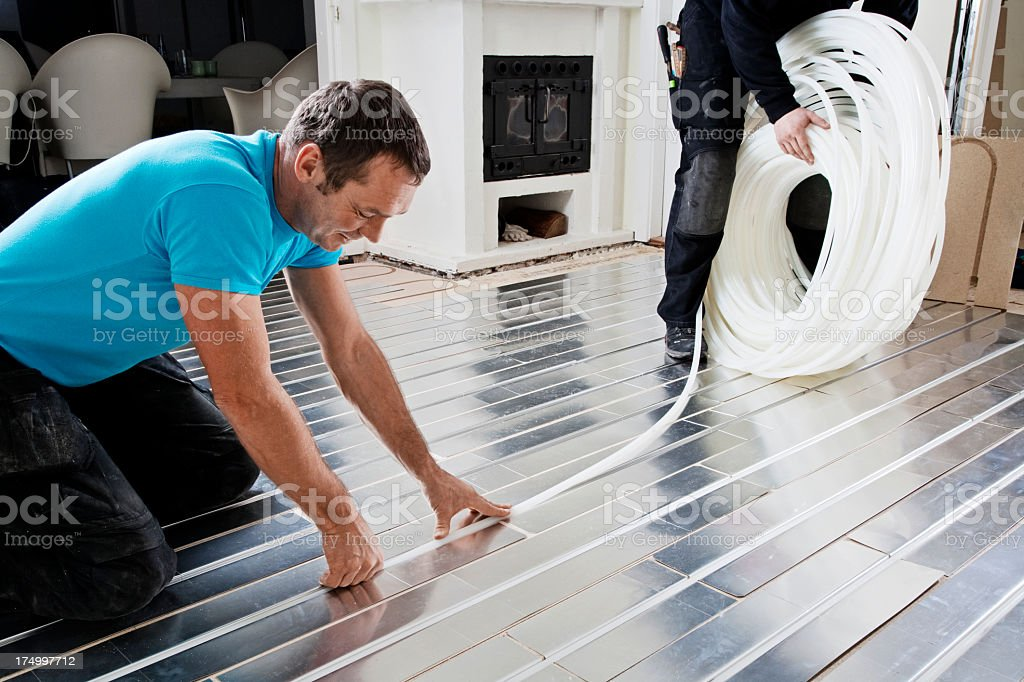 Fixing plastic tubing into metal sheet grooves for underfloor heating stock photo