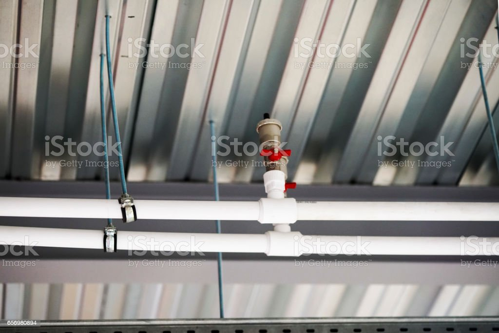 fixing the pipes under the ceiling stock photo