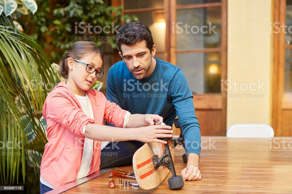 Fixing the skateboard with a helping dad. stock photo