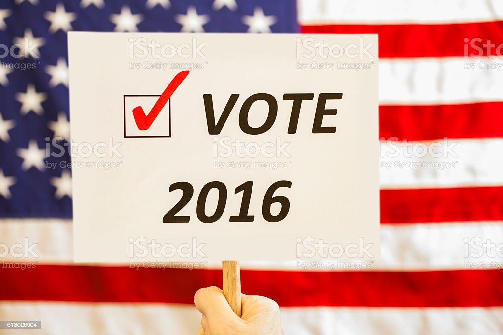 USA flag and 2016 vote sign held at political rally. stock photo