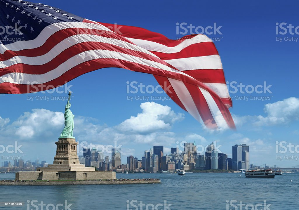 US flag and Statue of Liberty with New York behind royalty-free stock photo