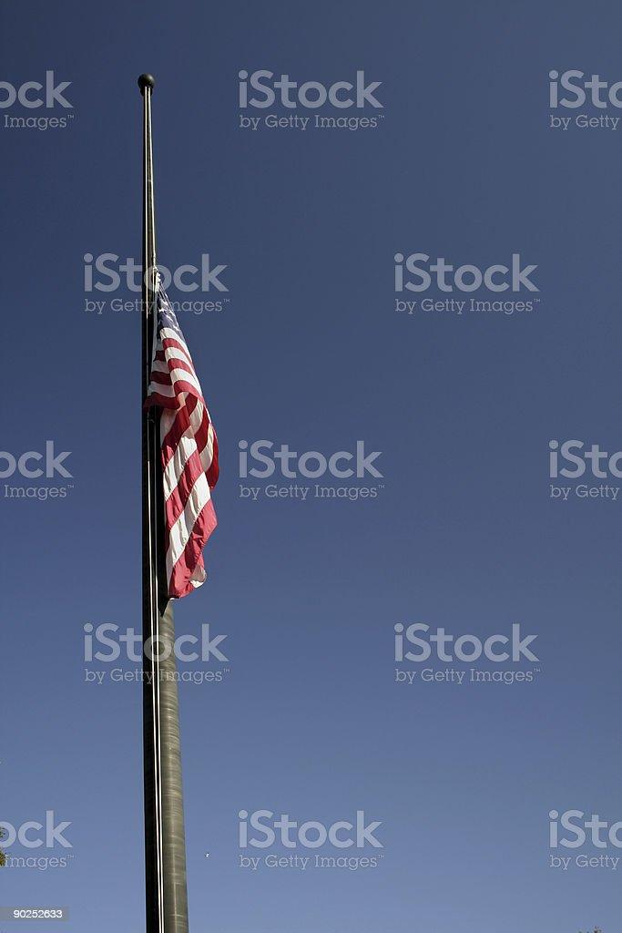 Flag at Half Mast Against Blue Sky stock photo