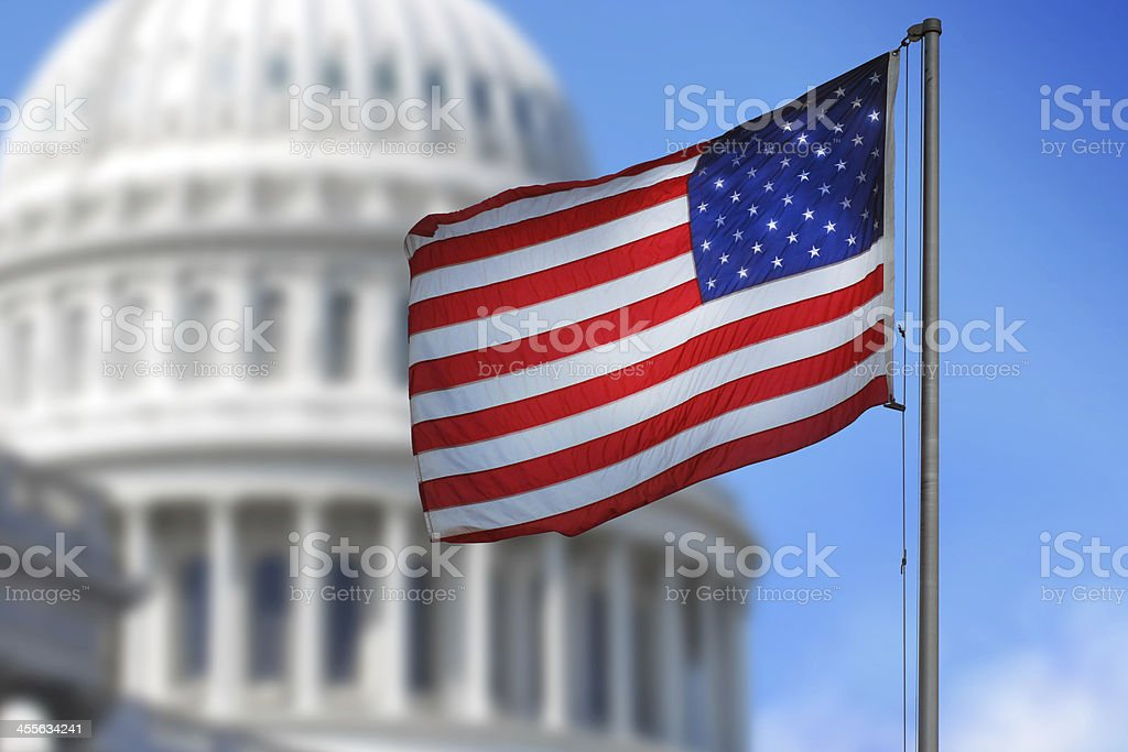 USA flag blowing in wind in front of Capitol Hill's dome stock photo