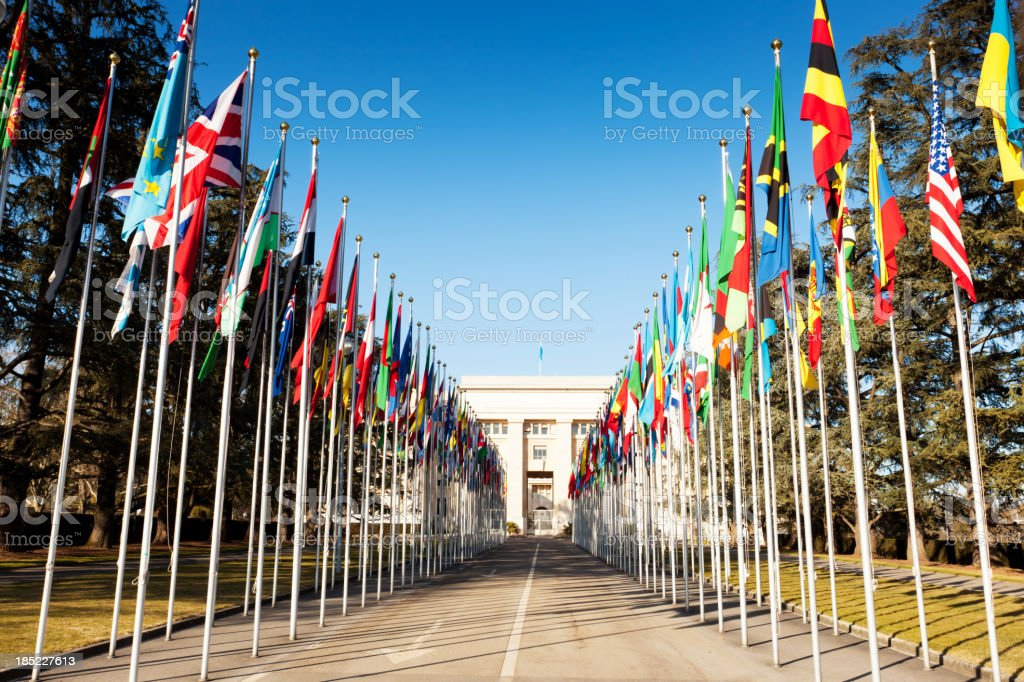flag draped roadway behind United nations building stock photo
