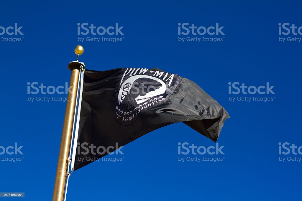 POW-MIA Flag Flying in Brilliant Blue Sky stock photo