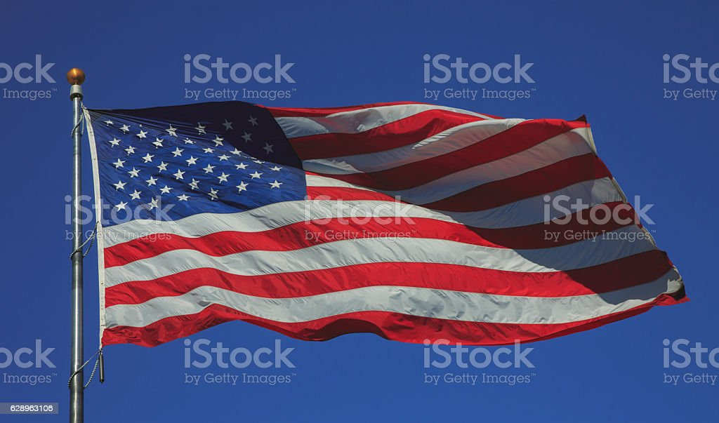 US flag flying in strong wind in a blue sky stock photo