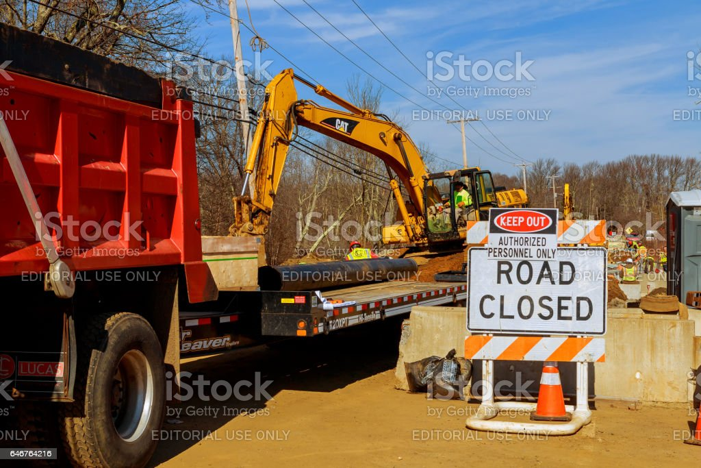 flag man points to a road closed sign on a highway stock photo