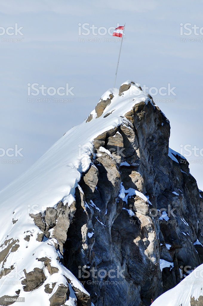 Flag of Austria on a cliff in the Alps stock photo
