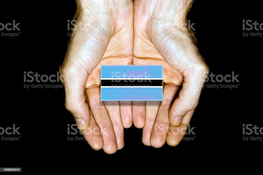Flag of Botswana in hands on black background stock photo