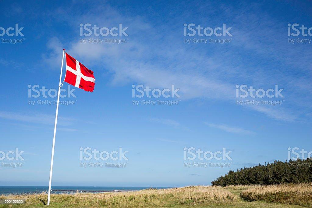 flag of Denmark waving on white pole against blue sky stock photo