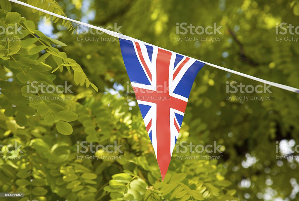 Flag of Great Britain with trees in the background royalty-free stock photo