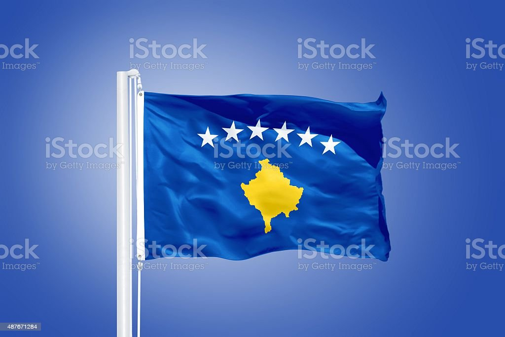 Flag of Kosovo flying against a blue sky stock photo