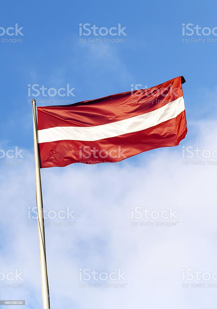 Flag of Latvia above blue sky with clouds stock photo