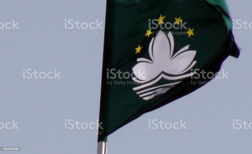 Flag Of Macau Waving Against Blue Sky stock photo