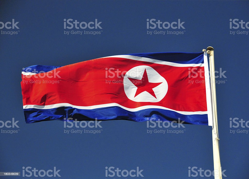 flag of North Korea flying in a deep blue sky stock photo
