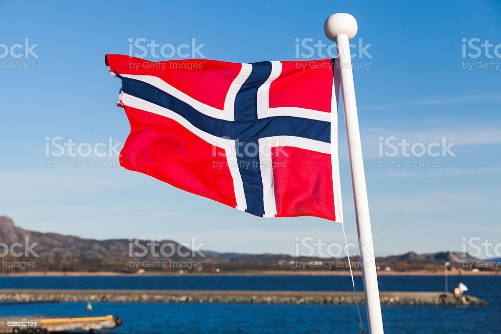 Flag of Norway waving over blue sky stock photo