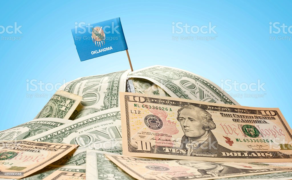 Flag of Oklahoma sticking in american banknotes.(series) stock photo