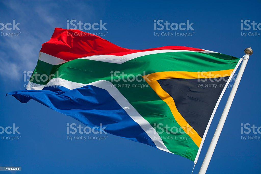 Flag of South Africa blowing in wind against blue sky stock photo