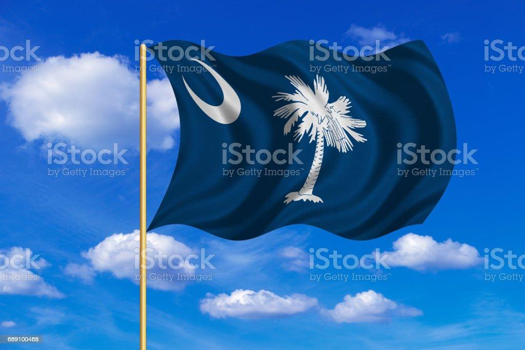 Flag of South Carolina waving on blue sky backdrop stock photo