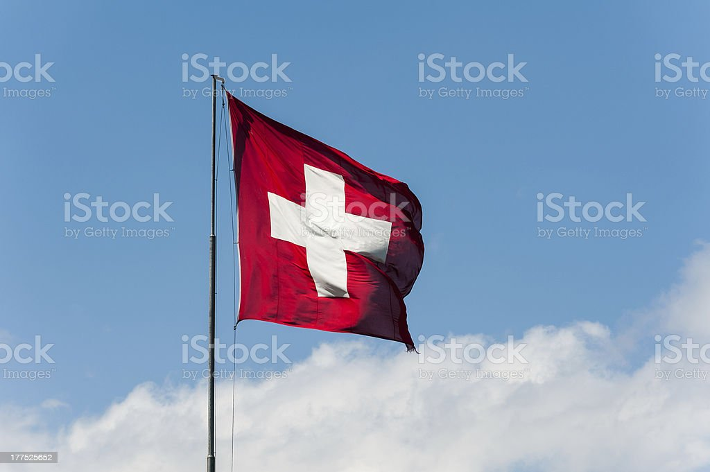Flag of Switzerland fluttering against a blue and white sky stock photo