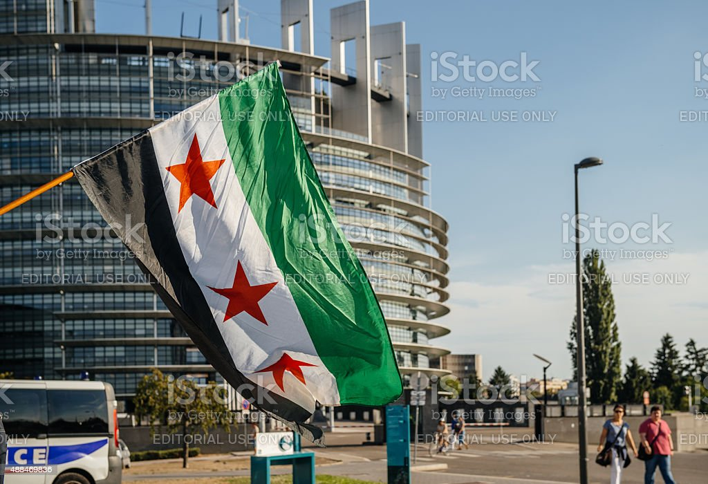 Flag of Syria with Police car and European Parliament Building stock photo