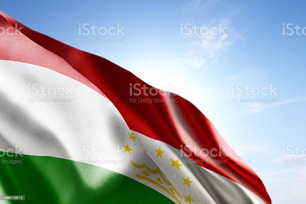 Flag of Tajikistan waving in the wind stock photo