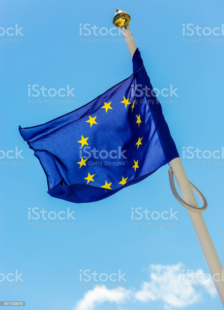 flag of the European Union with clouds underneath symbolizing darkening stock photo
