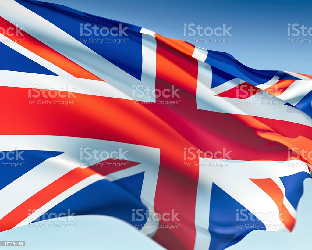 Flag of the United Kingdom in the wind behind a blue sky stock photo