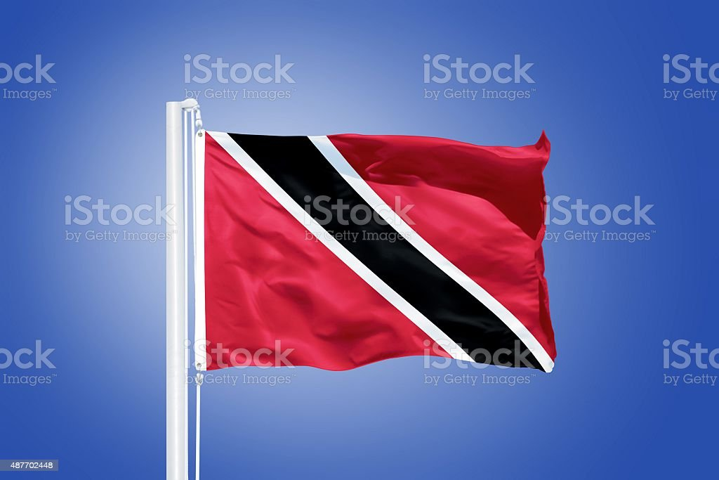 Flag of Trinidad and Tobago flying against a blue sky stock photo