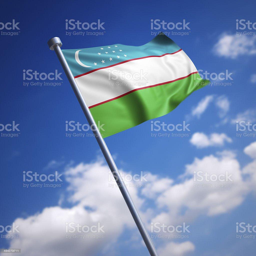 Flag of Uzbekistan against blue sky stock photo
