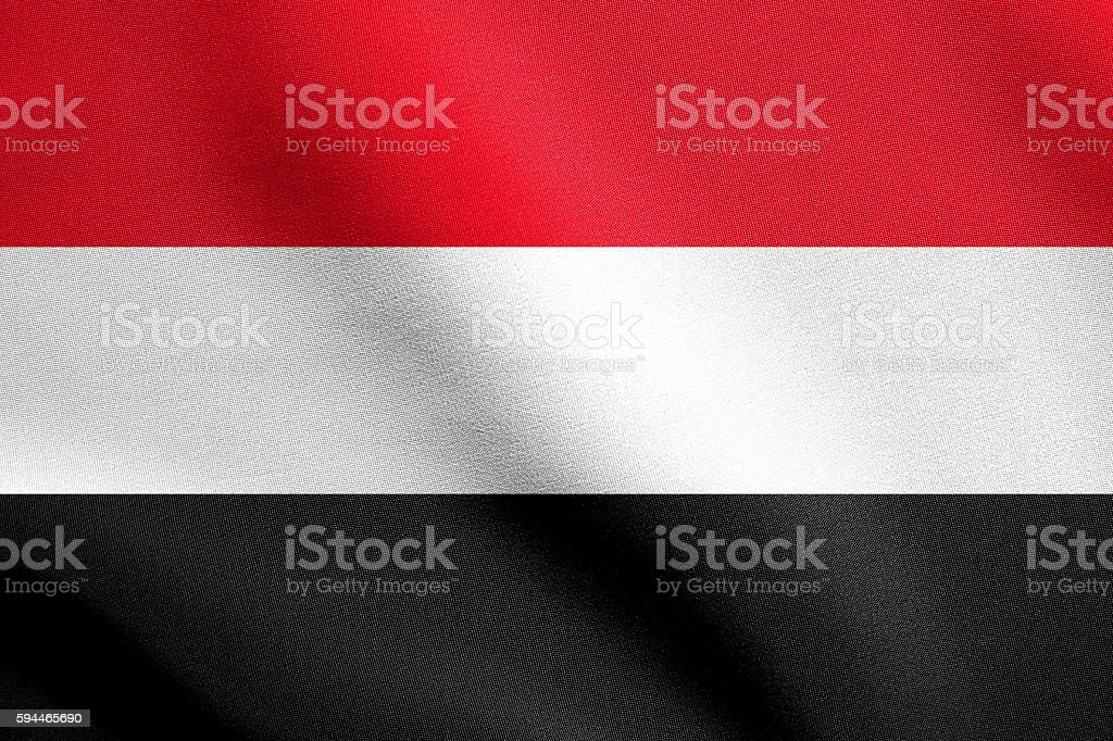 Flag of Yemen waving in wind with fabric texture stock photo