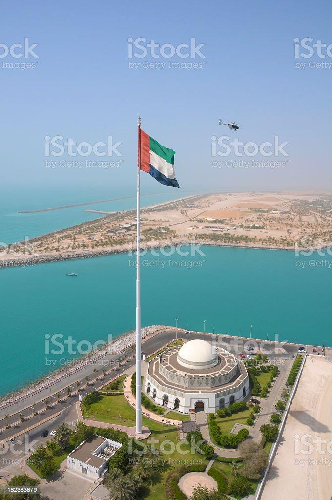A flag on a flagpole against a blue harbor stock photo
