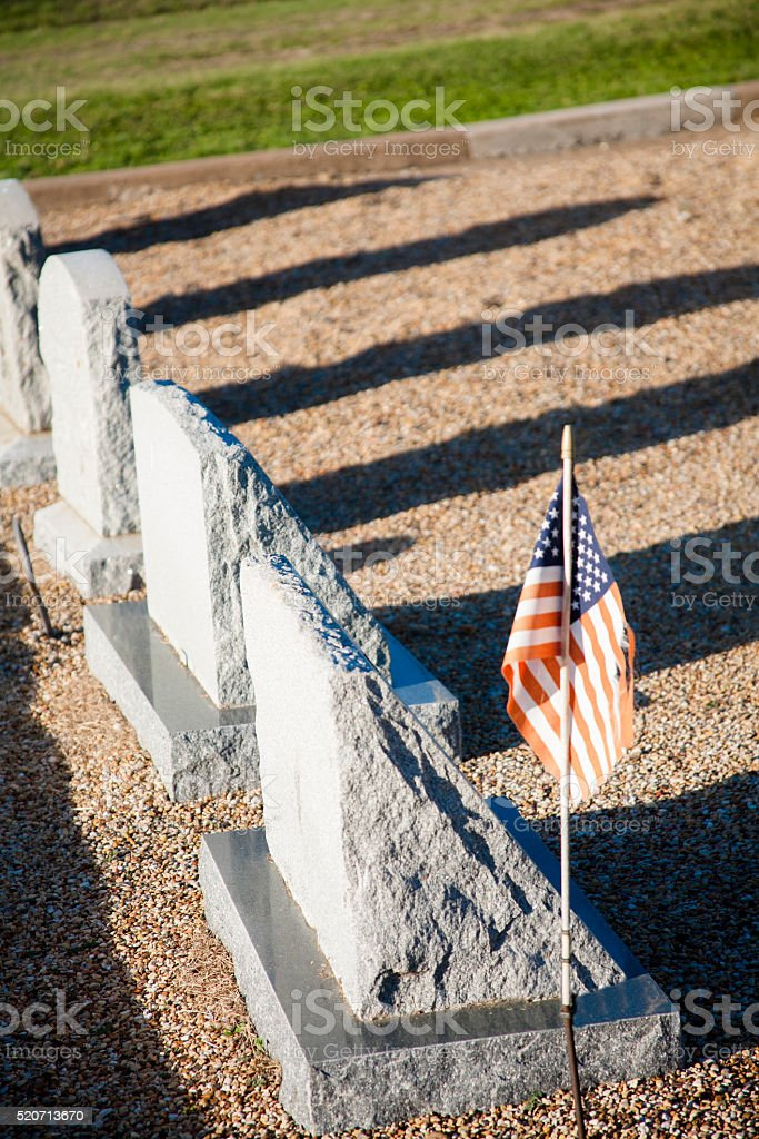 USA flag on grave, tombstone in cemetary.  Other headstones. stock photo