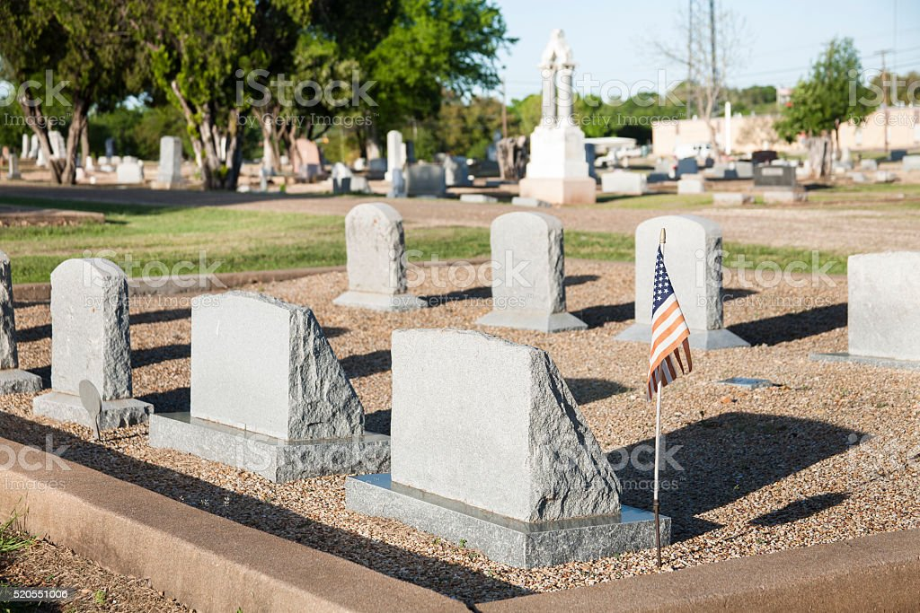 USA flag on grave, tombstones in cemetary.  Other headstones. stock photo
