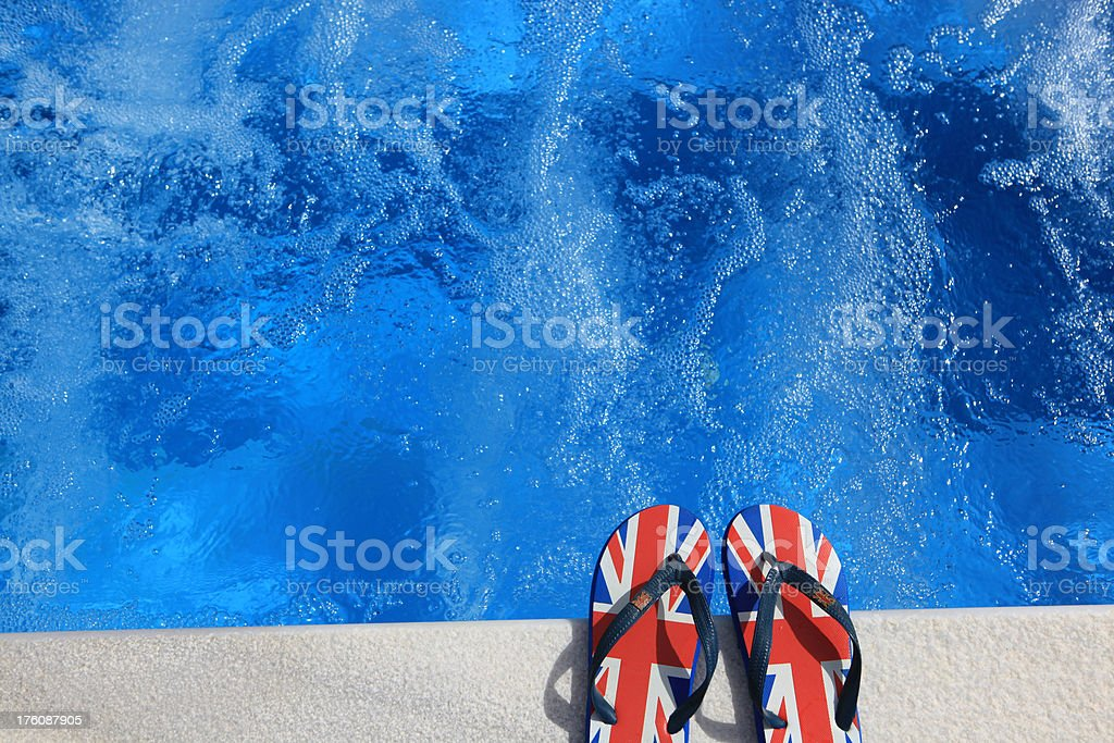 UK flag or Union Jack flip flops by the pool royalty-free stock photo