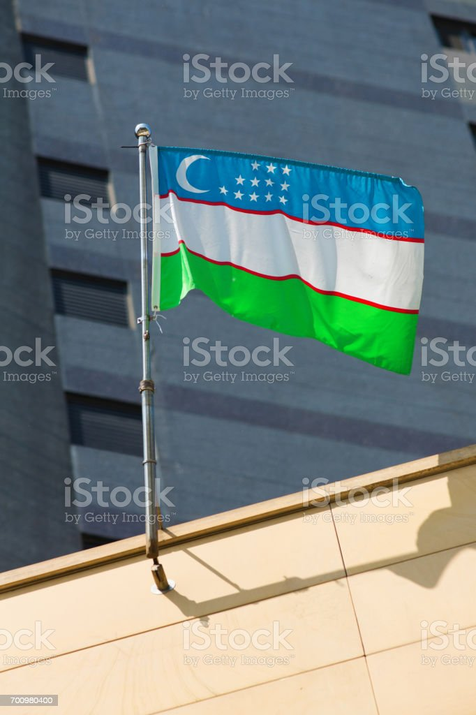 Flag or Uzbekistan floating in front of office building stock photo