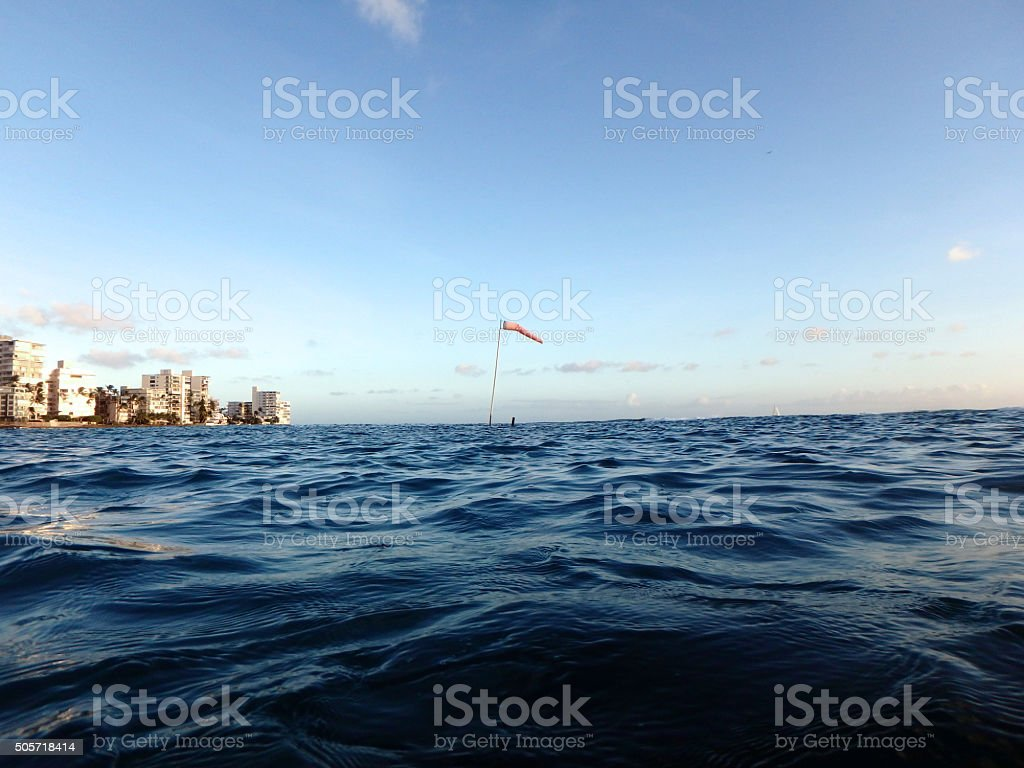 Flag pole with wind sock rises above the wavy water stock photo