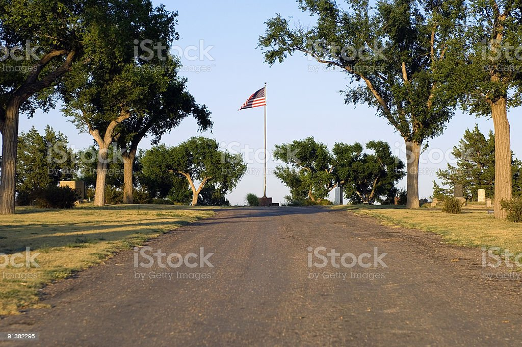 Flag, road, trees, tombstones royalty-free stock photo