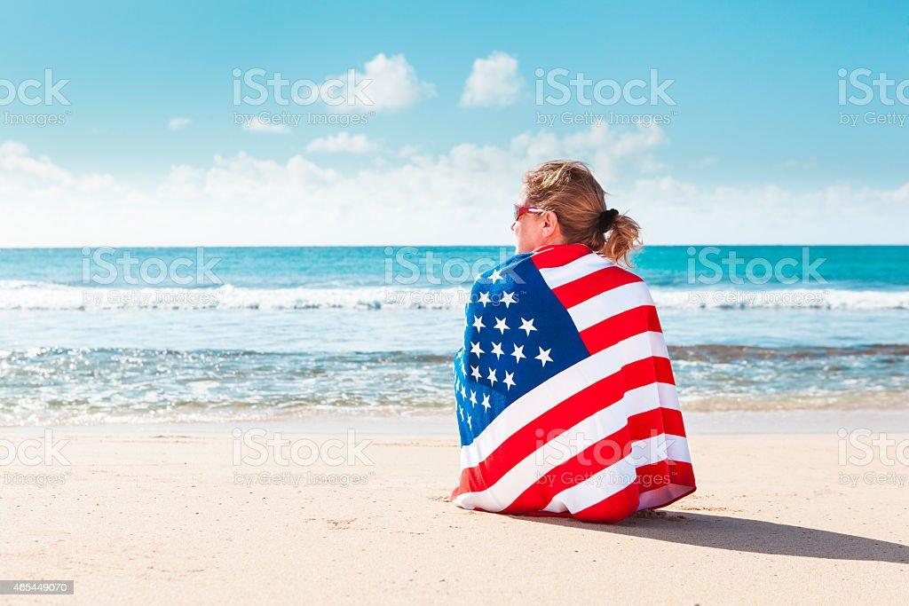 USA Flag Towel Wrapped Woman Vacationing on Hawaiian Tropical Beach stock photo