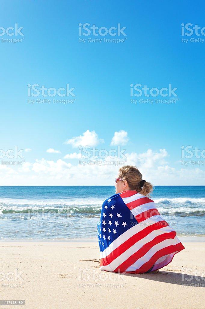 USA Flag Towel Wrapped Woman Vacationing on Tropical Hawaiian Beach stock photo