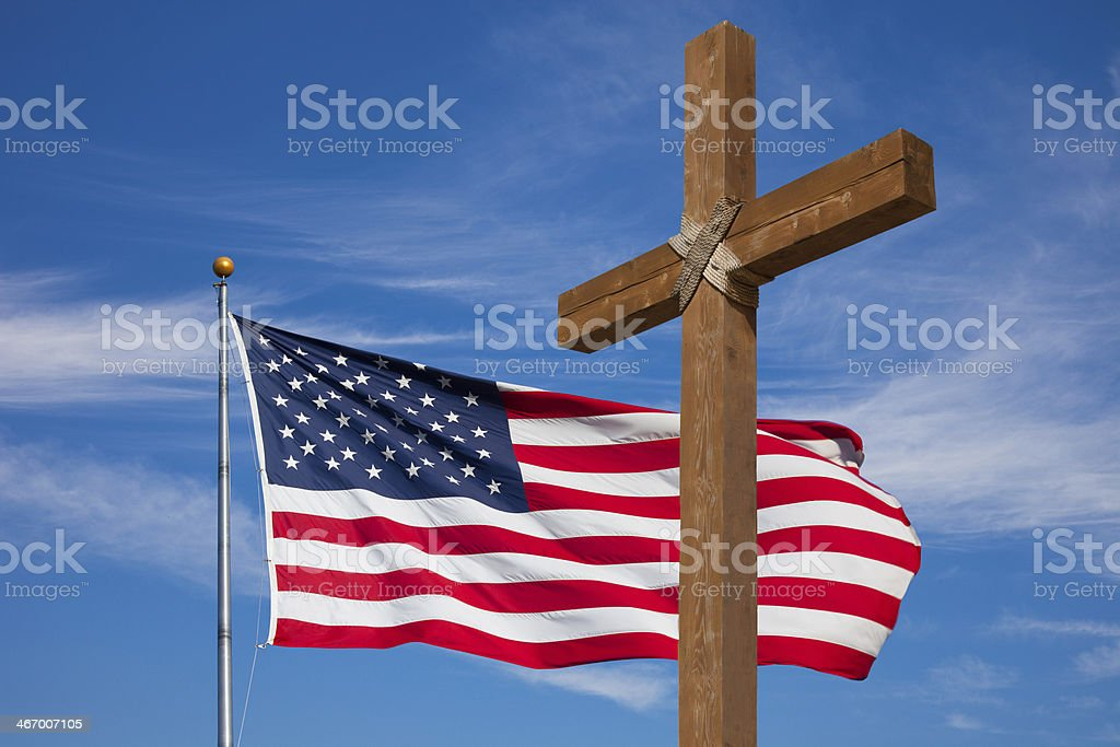 USA flag waving and a wooden cross against blue sky stock photo