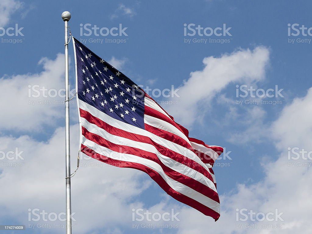 US Flag Waving in Blue Cloudy Sky stock photo
