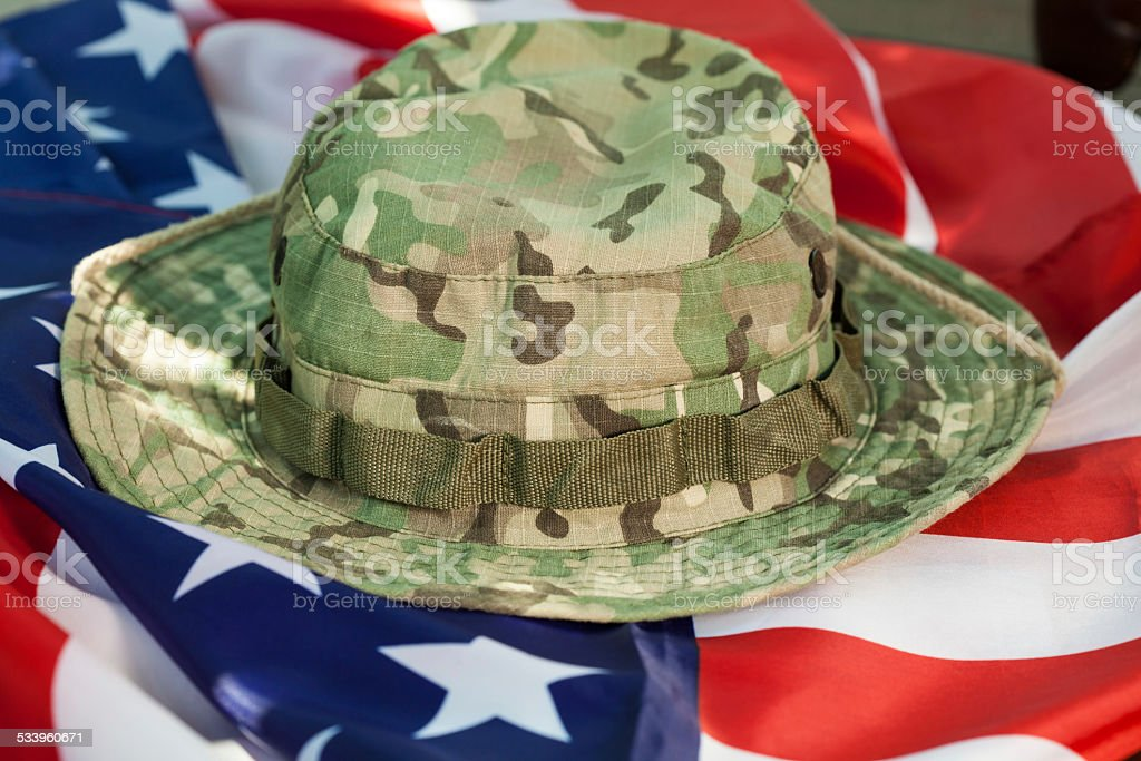 US flag with camouflage combat hat stock photo