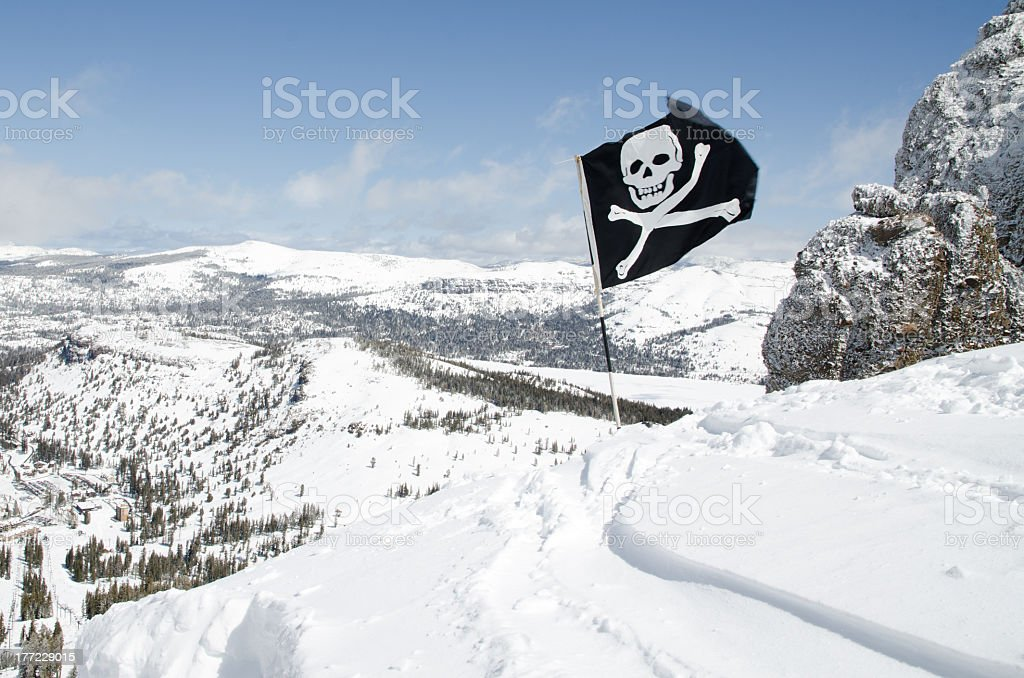 Flag with skull and bones. Warning sign on alpine summit royalty-free stock photo